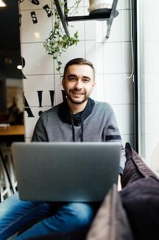 Homem bonito com laptop em um café