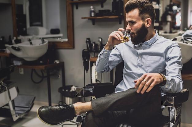 Homem bonito com licor na barbearia