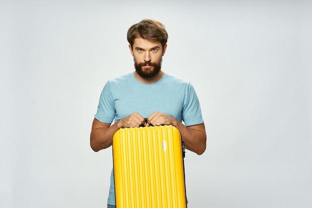 Homem bonito com mala amarela sobre turismo de viagens de fundo claro