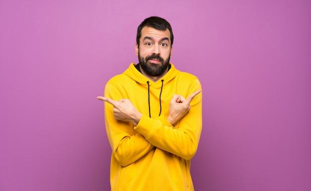 Homem bonito com moletom amarelo apontando para as laterais tendo dúvidas