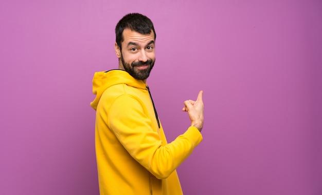 Homem bonito com moletom amarelo apontando para trás