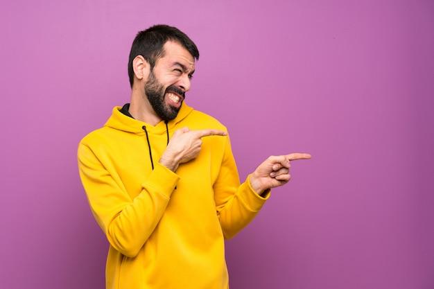 Homem bonito com moletom amarelo assustado e apontando para o lado