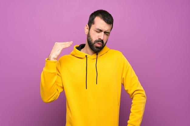 Homem bonito com moletom amarelo com expressão cansada e doente