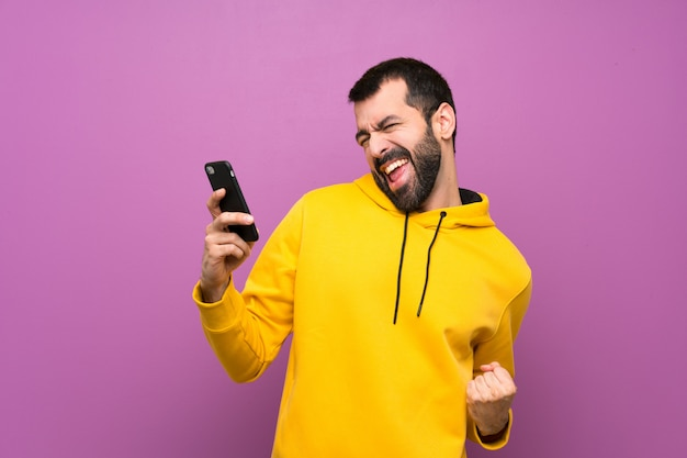 Homem bonito com moletom amarelo com telefone em posição de vitória