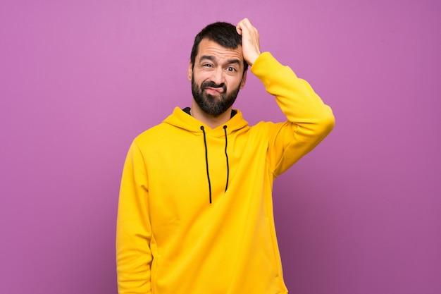 Homem bonito com moletom amarelo com uma expressão de frustração e não compreensão