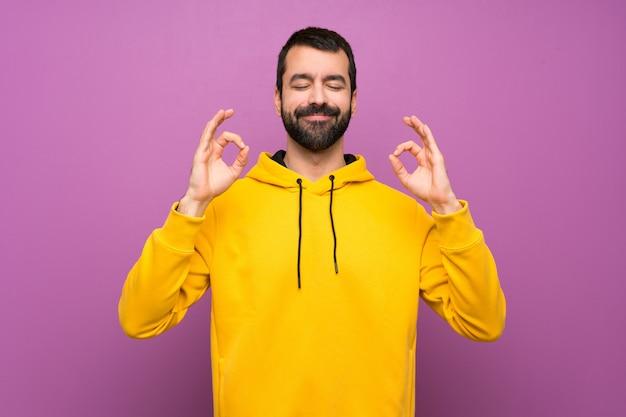 Homem bonito com moletom amarelo em pose de zen