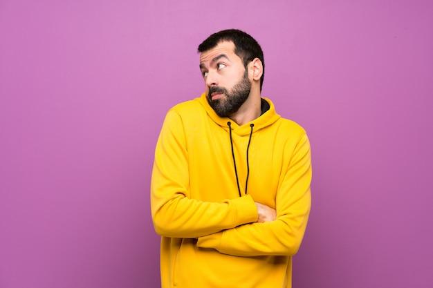 Homem bonito com moletom amarelo fazendo dúvidas gesto enquanto levanta os ombros