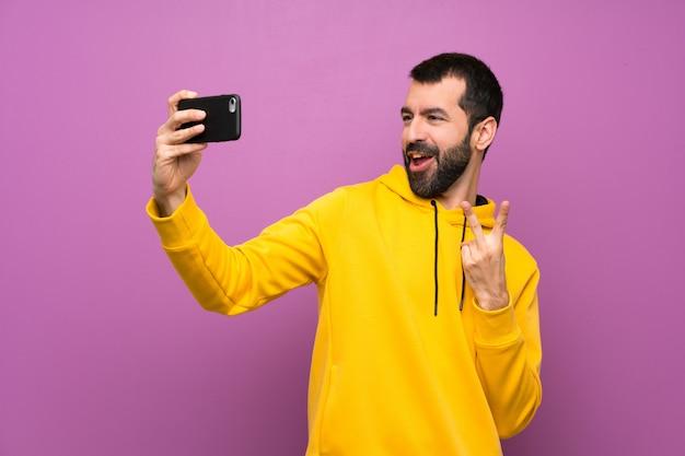 Homem bonito com moletom amarelo fazendo um selfie