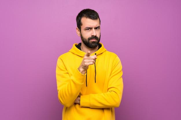 Homem bonito com moletom amarelo frustrado e apontando para a frente