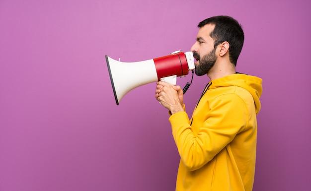 Homem bonito com moletom amarelo gritando através de um megafone