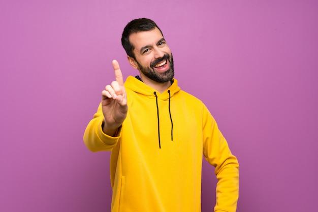 Homem bonito com moletom amarelo mostrando e levantando um dedo