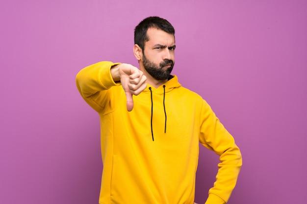 Homem bonito com moletom amarelo mostrando o polegar para baixo com expressão negativa