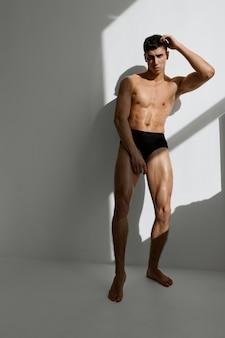 Homem bonito com o corpo bombado e calcinha preta posando