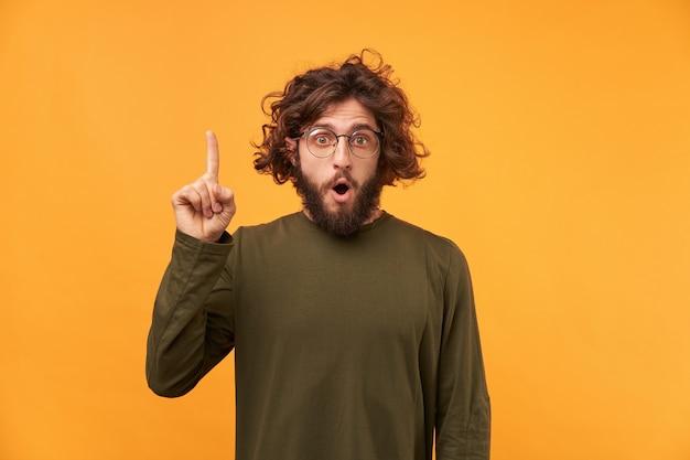 Homem bonito com o dedo levantado e olhando para a frente enquanto encosta na parede amarela