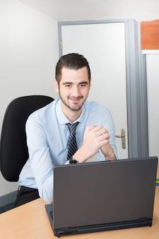 Homem bonito com o laptop na mesa em dia de trabalho e feliz