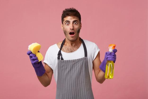 Homem bonito com o rosto sujo, usando avental e luvas, segurando uma esponja e spray de limpeza, com expressão chocada, percebendo o quanto ele deve limpar. homem intrigado fazendo tarefas domésticas isoladas