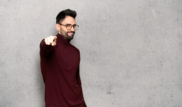 Homem bonito com óculos aponta o dedo para você com uma expressão confiante sobre parede texturizada