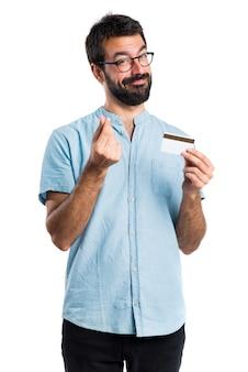 Homem bonito com óculos azuis segurando um cartão de crédito