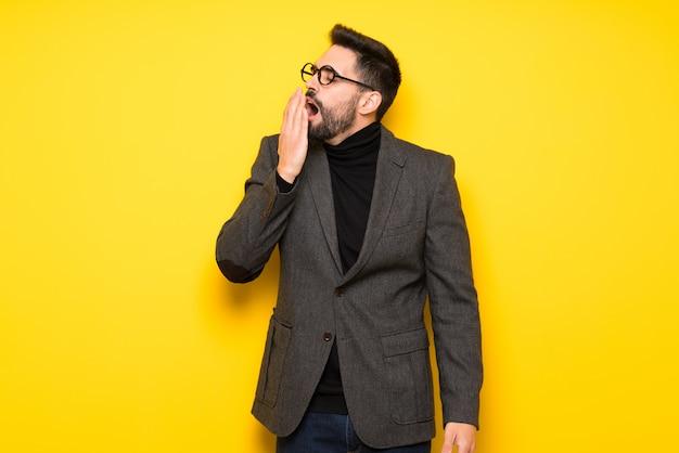 Homem bonito com óculos bocejando e cobrindo a boca aberta com a mão