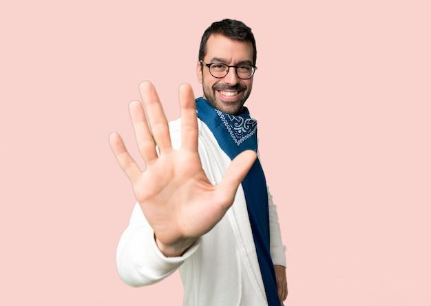 Homem bonito com óculos contando cinco dedos