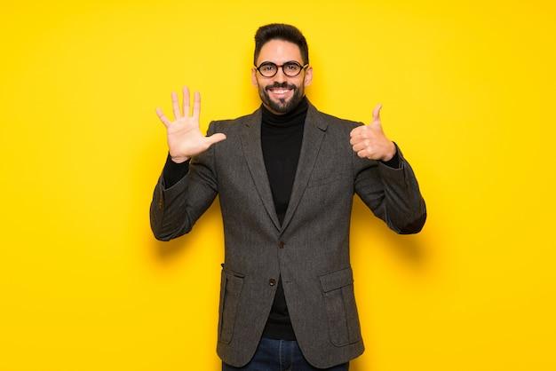 Homem bonito com óculos contando seis dedos