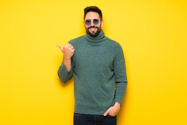 Homem bonito com óculos de sol apontando para o lado para apresentar um produto