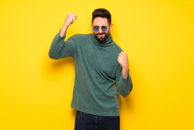 Homem bonito com óculos de sol, celebrando uma vitória