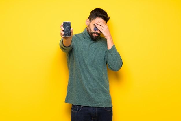 Homem bonito com óculos de sol com conturbado segurando smartphone quebrado
