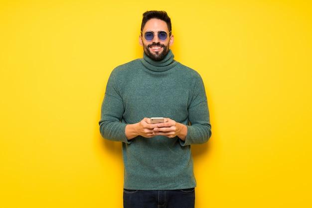Homem bonito com óculos de sol, enviando uma mensagem com o celular