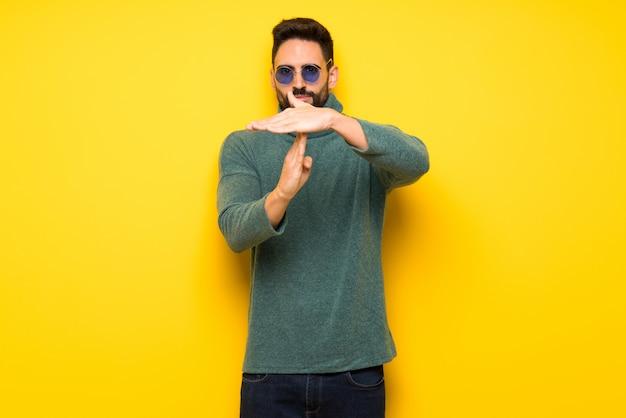 Homem bonito com óculos de sol fazendo parada gesto com a mão para parar um ato