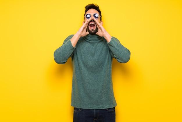 Homem bonito com óculos de sol gritando e anunciando algo