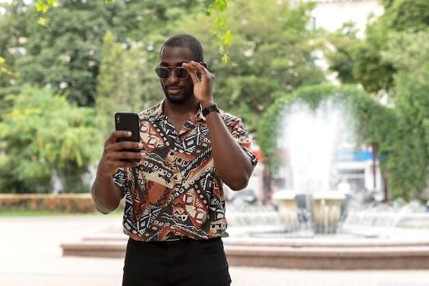 Homem bonito com óculos escuros usando smartphone moderno ao ar livre