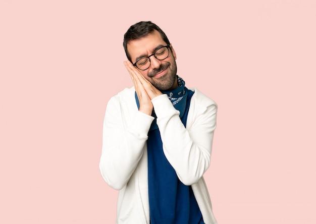 Homem bonito com óculos fazendo gesto de sono na expressão dorable no fundo rosa isolado