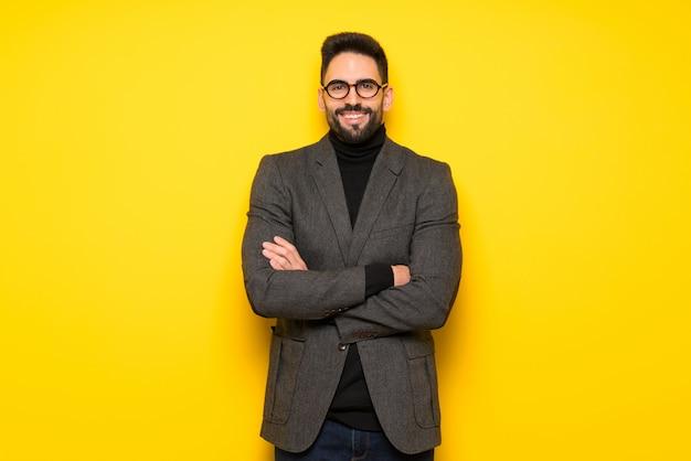 Homem bonito com óculos, mantendo os braços cruzados em posição frontal