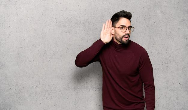 Homem bonito com óculos, ouvindo algo, colocando a mão na orelha
