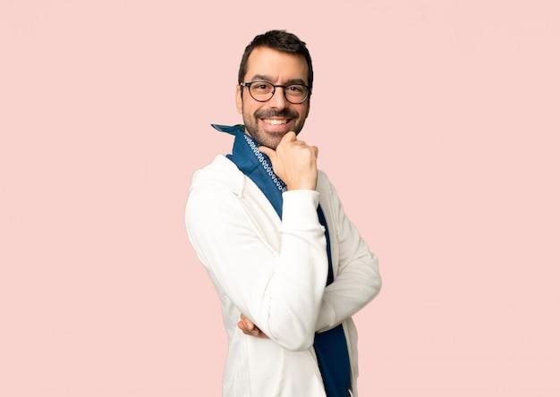 Homem bonito com óculos sorrindo e olhando para a frente com cara confiante