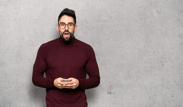 Homem bonito com óculos surpreendeu e enviando uma mensagem texturizada de parede