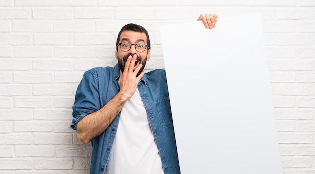 Homem bonito com parede de tijolo branco de barba segurando um cartaz vazio