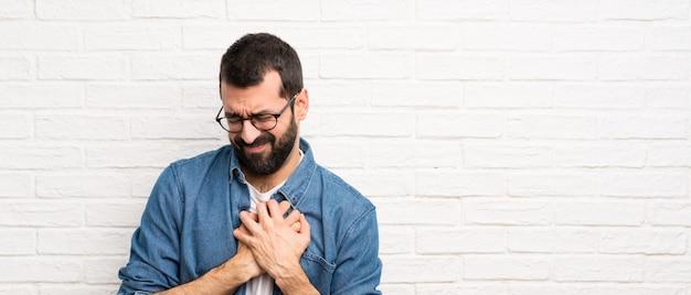 Homem bonito com parede de tijolo branco de barba, tendo uma dor no coração
