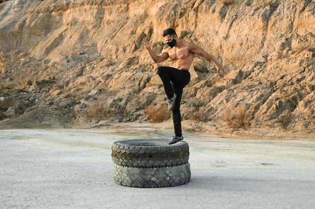 Homem bonito com pernas de treinamento de corpo atlético em pneus ao ar livre. cara forte usando máscara protetora e calça preta. exercícios de esporte ao ar livre.
