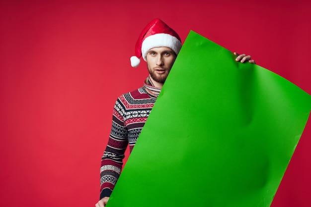 Homem bonito com roupas de ano novo anunciando cópia espaço fundo vermelho