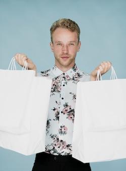 Homem bonito com sacolas de compras, olhando para a câmera