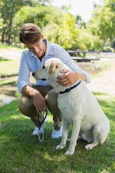 Homem bonito com seu labrador no parque