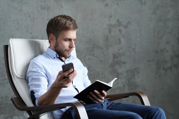 Homem bonito com smartphone e notebook