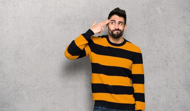 Homem bonito com suéter listrado com problemas fazendo gesto de suicídio ao longo da parede texturizada