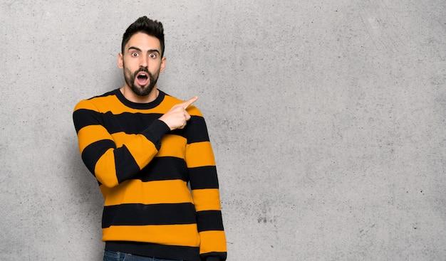 Homem bonito com suéter listrado surpreendido e apontando o lado sobre a parede texturizada