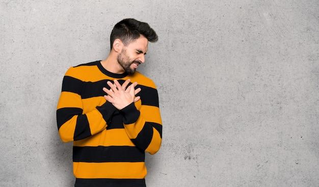 Homem bonito com suéter listrado, tendo uma dor no coração sobre a parede texturizada