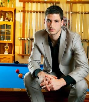 Homem bonito com terno sentado na piscina de bilhar