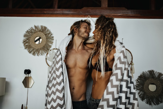 Homem bonito com torso nu abraça a namorada e a cobre com tapete listrado