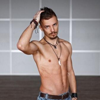 Homem bonito com torso nu e penteado perto da parede